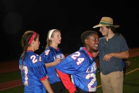 Senior Spencer Hoagland gives classmate Naomi Jones and others instructions for the second half of last year's Powderpuff game.